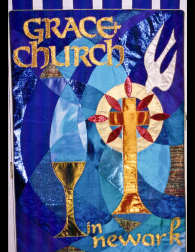 "The front of the Grace banner - started with ""graceful lines"" reflecting the colors of the stained glass windows and incorporating the chalice/font as central"