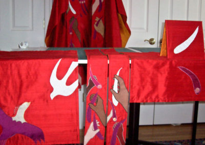 Pentecost set with flame/dove/phoenix and hands of many colors and sizes holding the feathers